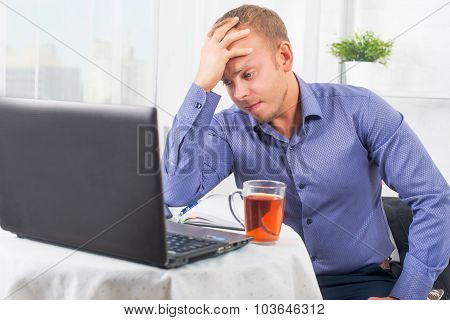 Young Businessman Working In The Office, Very Concerned, Solves Problem, And Leaned Head On His Hand