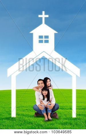 Asian Family At Field With Church Symbol