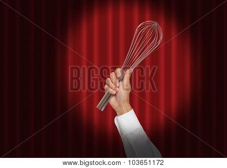 Hand holding a whisk under a spot light