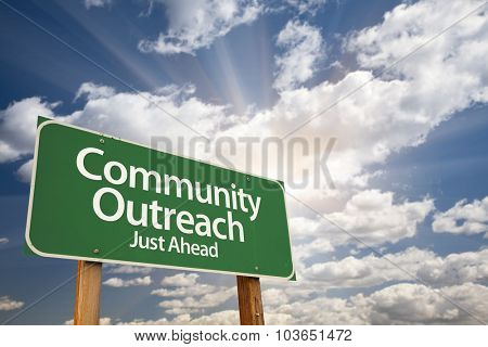 Community Outreach Green Road Sign With Dramatic Clouds and Sky.
