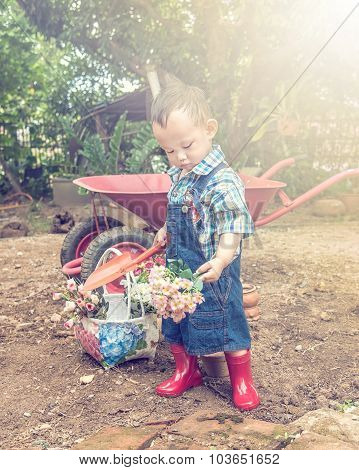 Baby Gardener. Asian Baby Boy Handle Garden Spoon , Light And Vintage Color Effect