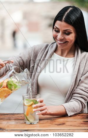 Young Woman Pouring Fresh Lemonade.