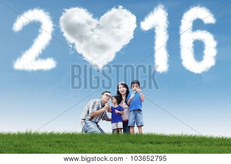 Family Playing Bubble At Field With Numbers 2016