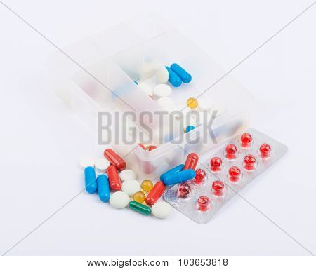 Tablets and capsules in blister packs on white background
