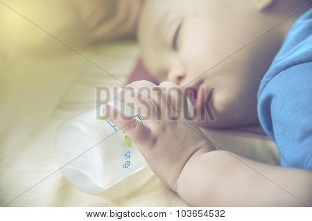 Closeup  Baby Hand And Finger . Baby  Holding Bottle While Sleeping