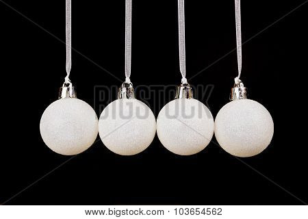 White Christmas Balls Hanging In A Row On Black Background