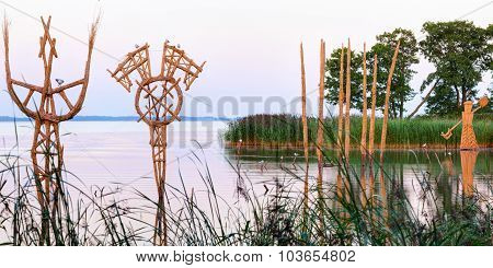 Straw (stubble) sculptures in the river creek. Lithuania.