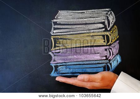 Man's Hand Holding A Stack Of Books Drawn With Chalk