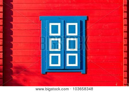 Red wooden wall with a colorful shutters