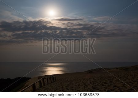 Sandy dunes with moon during nighttime. Baltic coast