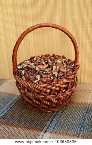 Rattan Basket With Walnut Kernels Is On A Checkered Napkin In Brown Tones