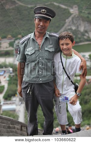 Beijing - June 12: Policman and boy On The Great Wall Of China On