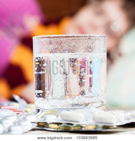 Glass With Dissolved Drug In And Pills On Table