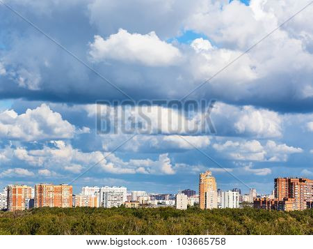 Low Blue Clouds Over Green Woods And Town
