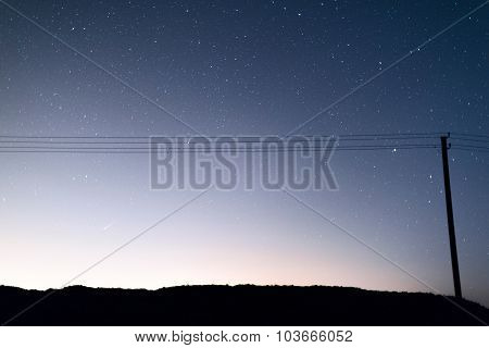 Telegraph pole with wires against the night sky full of stars.