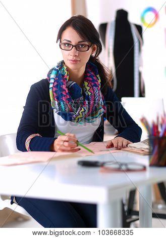 Dressmaker designing clothes pattern on paper