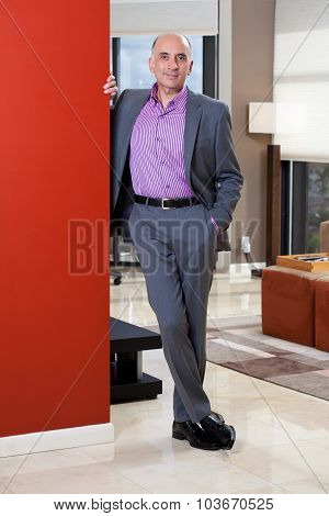 Handsome man standing by a red wall