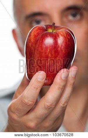 Man holding apple up close