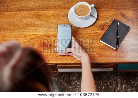 Woman With Mobile Phone In Cafe