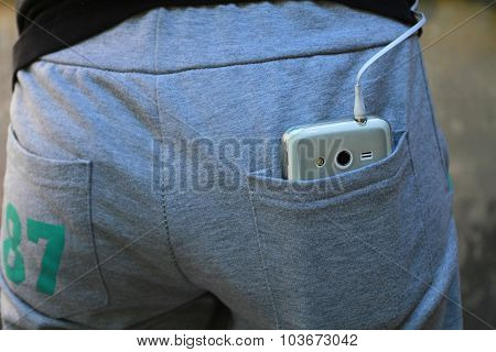 Mobile Phone With A Wire From The Headphones In The Back Pocket Of His Pants Sports