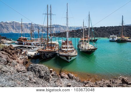 ourist excoursion boats at small port on volcano of Santorini