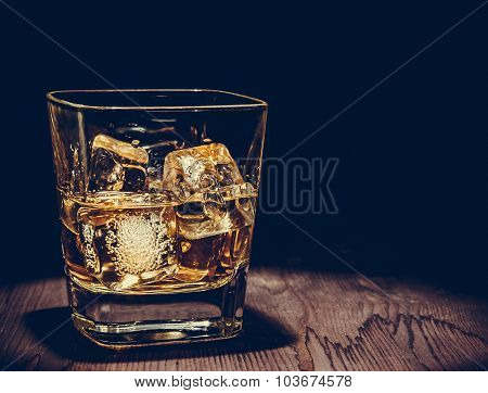 Glass Of Whiskey With Ice Cubes On Wood Table, Warm Atmosphere, Time Of Relax With Whisky