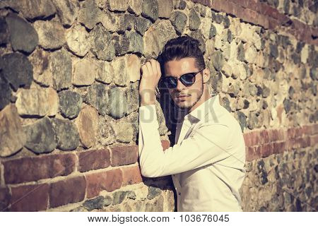 Attractive young man sitting against brick wall