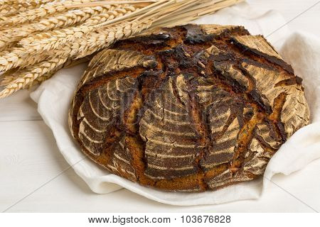 Hand Made Bread Loaf With Wheat Ears On White Wood