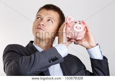 Businessman In Suit And Tie Shaking Funny Piggybank
