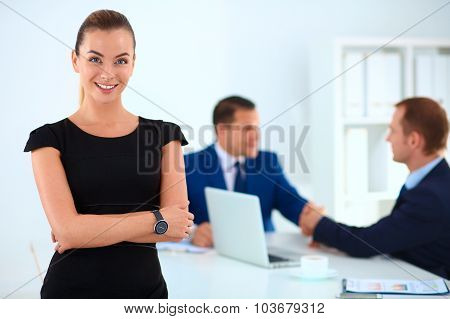 Portrait of a beautiful businesswoman standing in an office with colleagues shaking hands in the bac
