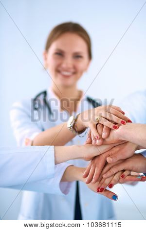 Team of doctors putting their hands together in a symbol of unity