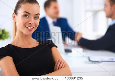 Portrait of a beautiful businesswoman standing in an office with colleagues in the background