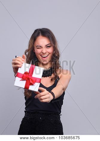 Young woman happy smile hold gift box in hands, isolated over grey background