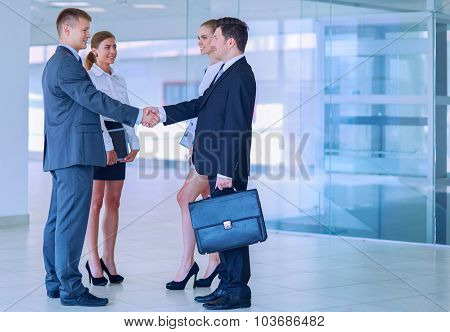 Full length image of two successful business men shaking hands with each other