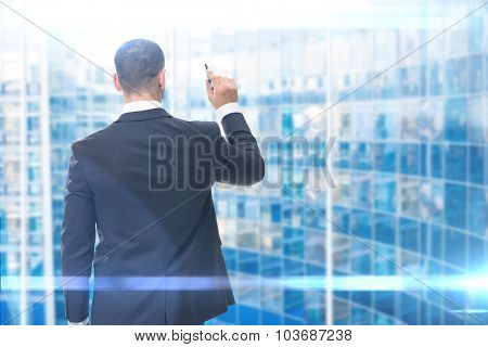 Backview of businessman writing something on the imaginary screen with marker, blue background