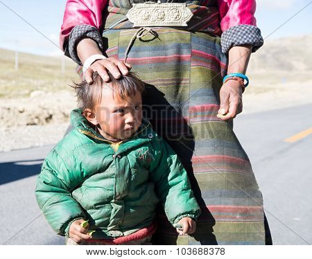 Tibetan kid in a steppe in Tibet.
