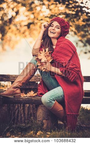 Beautiful woman wearing knitted coat in autumn park