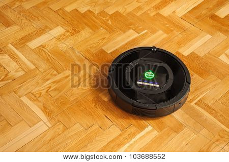 Robotic vacuum cleaner on parquet - technology housework