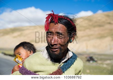 Tibetan farmer with his child in a steppe in Tibet.