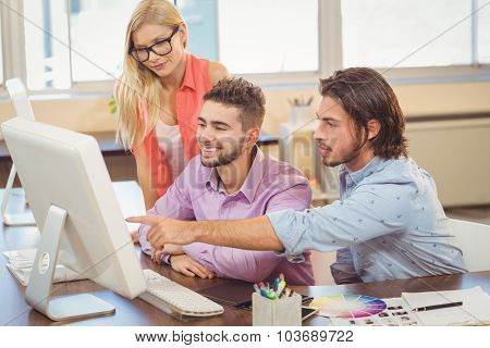 Businessman pointing on computer as colleagues looking at it in office
