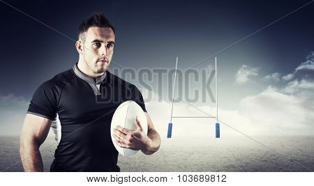 Tough rugby player holding ball against goals posts on pitch