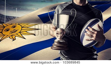 Midsection of successful rugby player holding trophy and ball against rugby stadium
