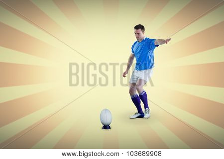 Rugby player doing a drop kick against linear background