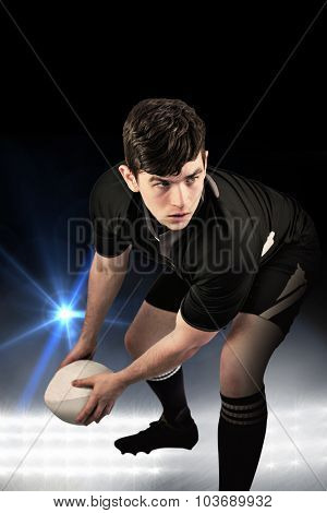 Rugby player about to throw the rugby ball against spotlights