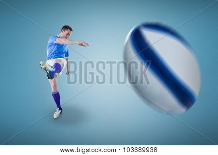 Rugby player kicking against blue background