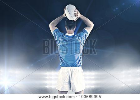 Rugby player about to throw a rugby ball against spotlights