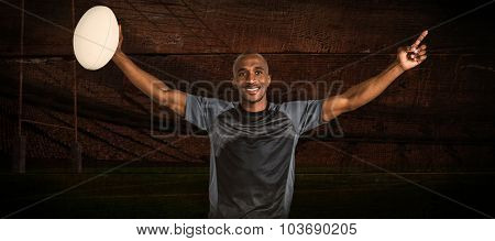 Confident sportsman with arms raised holding rugby ball against rugby stadium