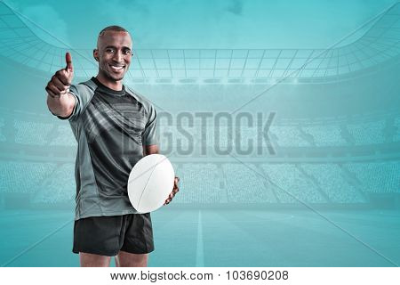 Portrait of confident rugby player smiling and showing thumbs up against blue vignette background