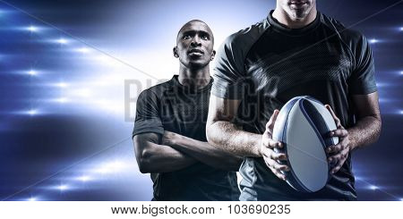 Thoughtful rugby player holding ball against spotlight