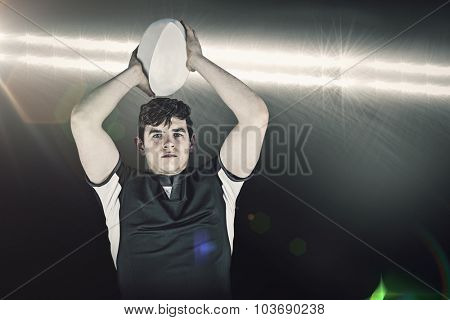 Portrait of a rugby player throwing a ball against spotlight